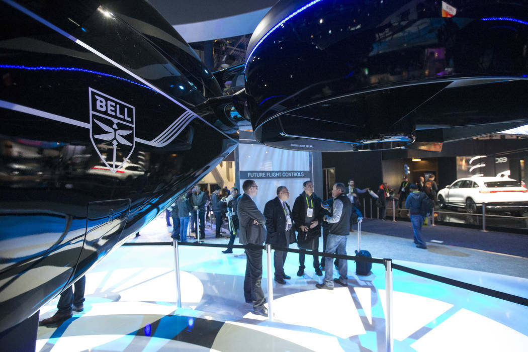 Attendees browse over the Bell Nexus, a hybrid-electric air taxi concept, on display on day one of CES at the Las Vegas Convention Center in Las Vegas on Tuesday, Jan. 8, 2019. Richard Brian Las V ...