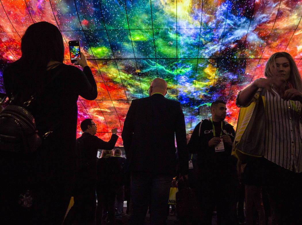Convention goers watch a huge LG visual display in the North Hall of the Las Vegas Convention Center during the second day of CES 2019 on Wednesday, Jan. 9, 2019, in Las Vegas. The four day tech e ...