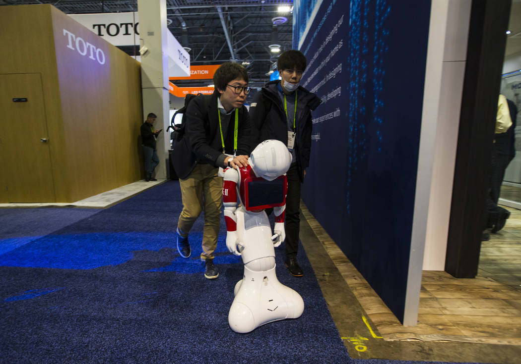 A robot from beauty and cosmetics company SK-II is escorted down a hallway for a presentation at the Sands Expo and Convention Center during CES in Las Vegas on Wednesday, Jan. 9, 2019. Chase Stev ...