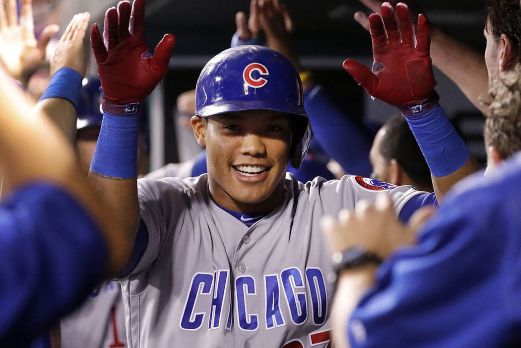 Chicago Cubs' Addison Russell is congratulated by teammates in the dugout after hitting a three-run home run during the seventh inning of a baseball game against the St. Louis Cardinals Wednesday, ...