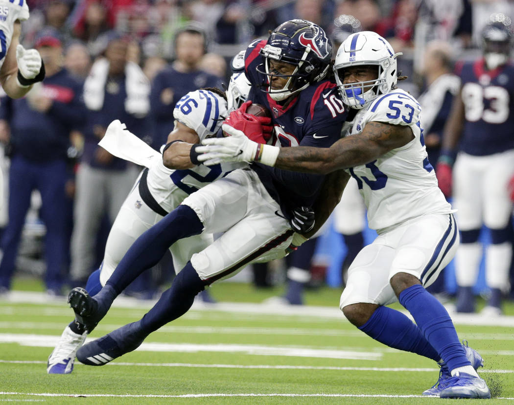 Houston Texans wide receiver DeAndre Hopkins (10) is hit by Indianapolis Colts strong safety Clayton Geathers (26) and linebacker Duke Ejiofor (53) after making a catch during the first half of an ...