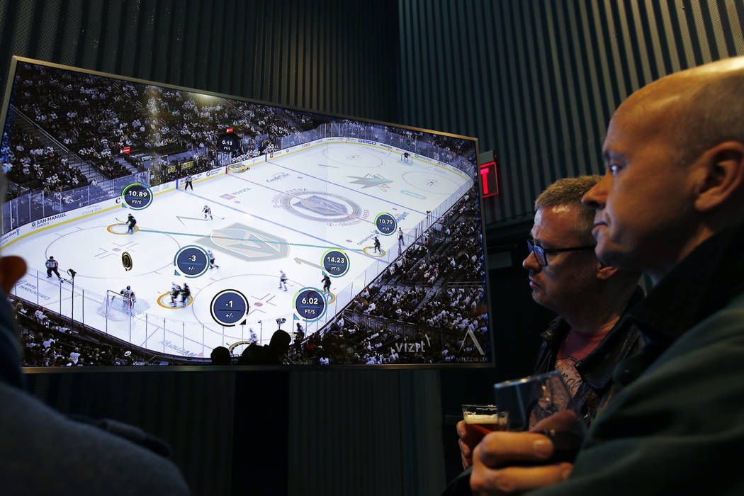 People watch real-time puck and player tracking technology on display during an NHL hockey game between the Vegas Golden Knights and the San Jose Sharks, in Las Vegas, Thursday, Jan. 10, 2019. The ...