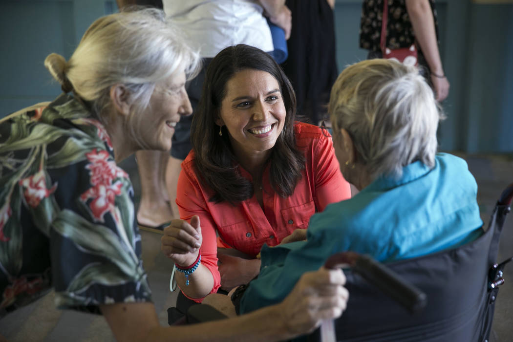 In this March 26, 2016, file photo, Rep. Tulsi Gabbard, D-Hawaii, center, greets voters as she waits with others to vote in the Democratic presidential caucus at a polling station at Kailua Interm ...