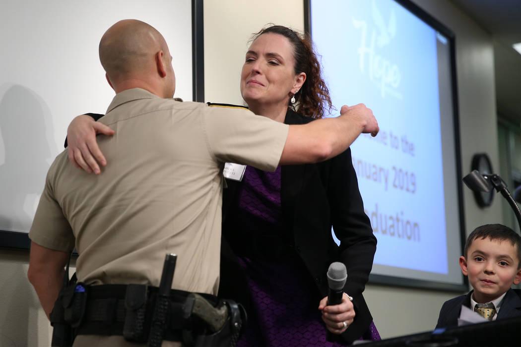 Program graduate Ashley Olivetti embraces Las Vegas police officer Tyler Hebb, during the Hope For Prisoners graduation at the Las Vegas Metropolitan Police Department headquarters in Las Vegas, F ...