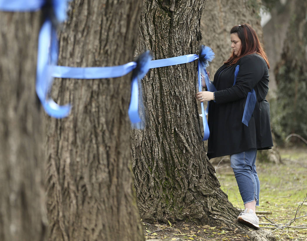 Vicky Oliverius ties blue ribbons on trees, Friday, Jan. 11, 2019, near the scene were Davis Police Officer Natalie Corona was shot and killed in Davis, Calif. (AP Photo/Rich Pedroncelli)