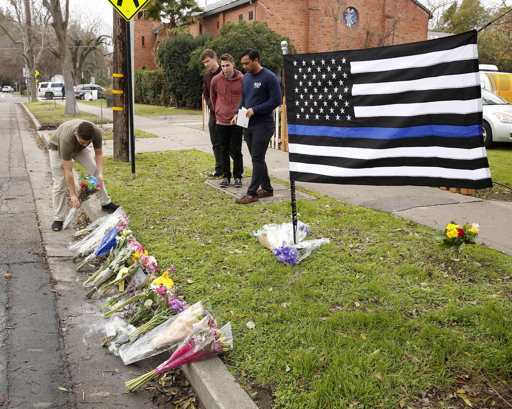 Alex Valenzuela, left, places flowers on a memorial for slain Davis Police Officer Natalie Corona, Friday, Jan. 11, 2019, in Davis, Calif. (AP Photo/Rich Pedroncelli)