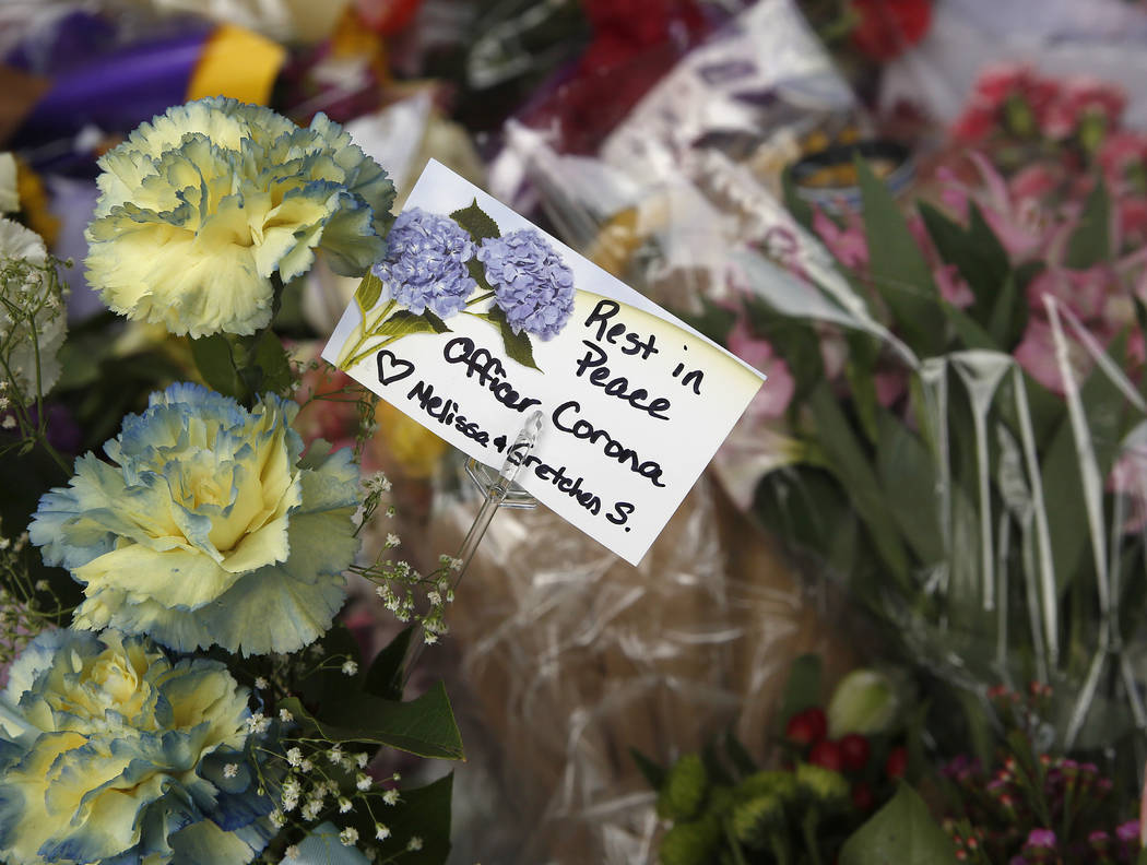 Flowers are seen on a memorial outside the Davis Police Department for slain Davis Police Officer Natalie Corona, Friday, Jan. 11, 2019, in Davis, Calif. (AP Photo/Rich Pedroncelli)