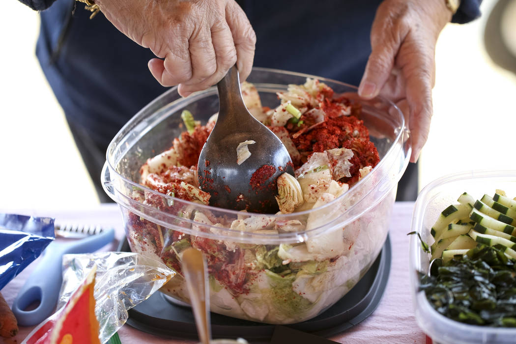 "Leonora Ching, author of the ""Pickle-Passion Cookbook,"" a book on Hawaiian and international recipes, demonstrates her spicy kimchi recipe during a volunteering event at the San Miguel C ..."