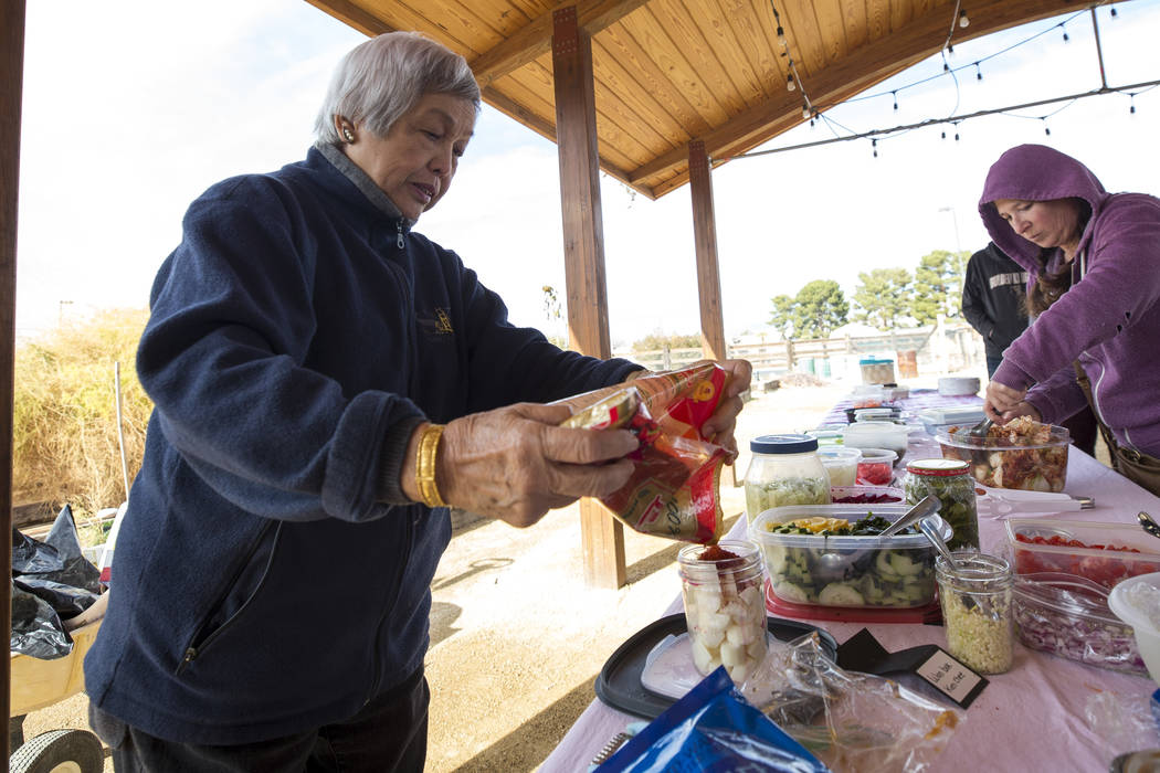 "Leonora Ching, left, author of the ""Pickle-Passion Cookbook,"" a book on Hawaiian and international recipes, demonstrates her daikon kimchi recipe during a volunteering event at the San M ..."