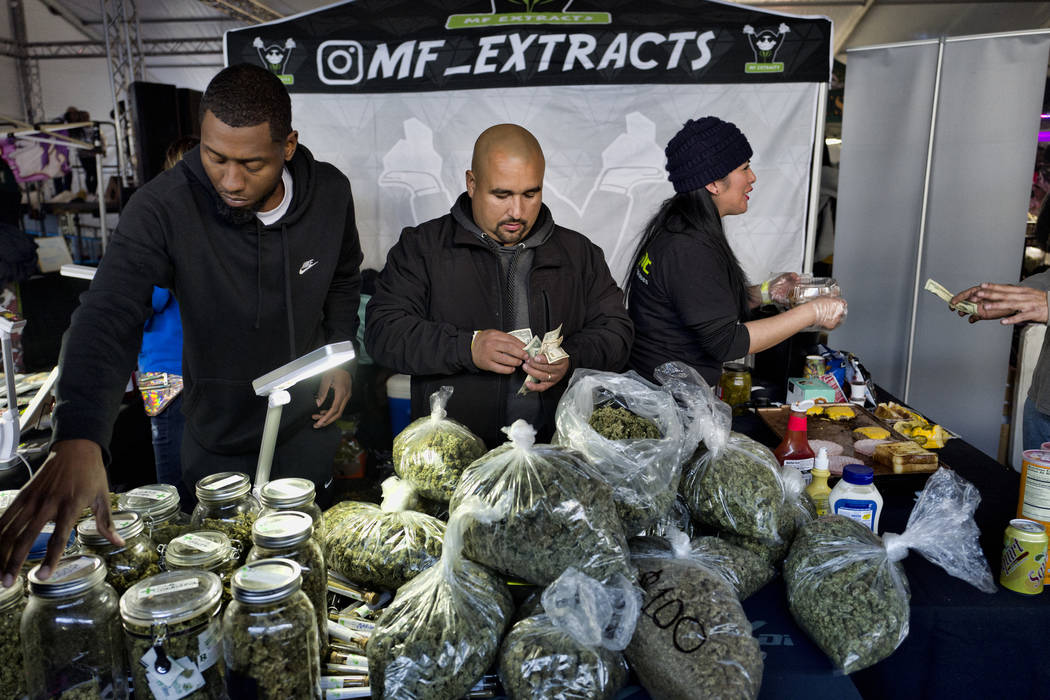 This Saturday, Dec. 29, 2018 file photo shows vendors from MF Extracts counting their intake of cash at their booth at Kushstock 6.5 festival in Adelanto Calif. (AP Photo/Richard Vogel,File)