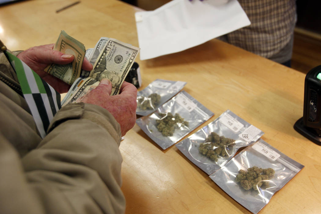 In this Monday, Jan. 1, 2018 file photo, a customer purchases marijuana at the Harborside marijuana dispensary in Oakland, Calif., on the first day that recreational marijuana was sold legally in ...