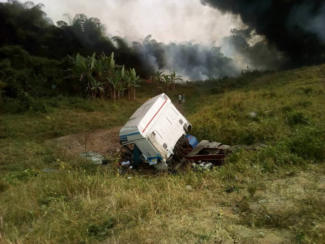 In this photo taken with a phone on Friday, Jan. 11, 2019, people gather at the site of an oil tanker explosion in Odukpani, Nigeria. An overturned oil tanker exploded in Nigeria while dozens of p ...