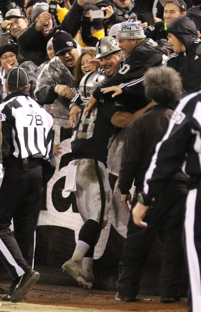 Oakland Raiders running back Doug Martin (28) scores a touchdown against the Denver Broncos and celebrates with fans during the first half of an NFL game in Oakland, Calif., Monday, Dec. 24, 2018. ...