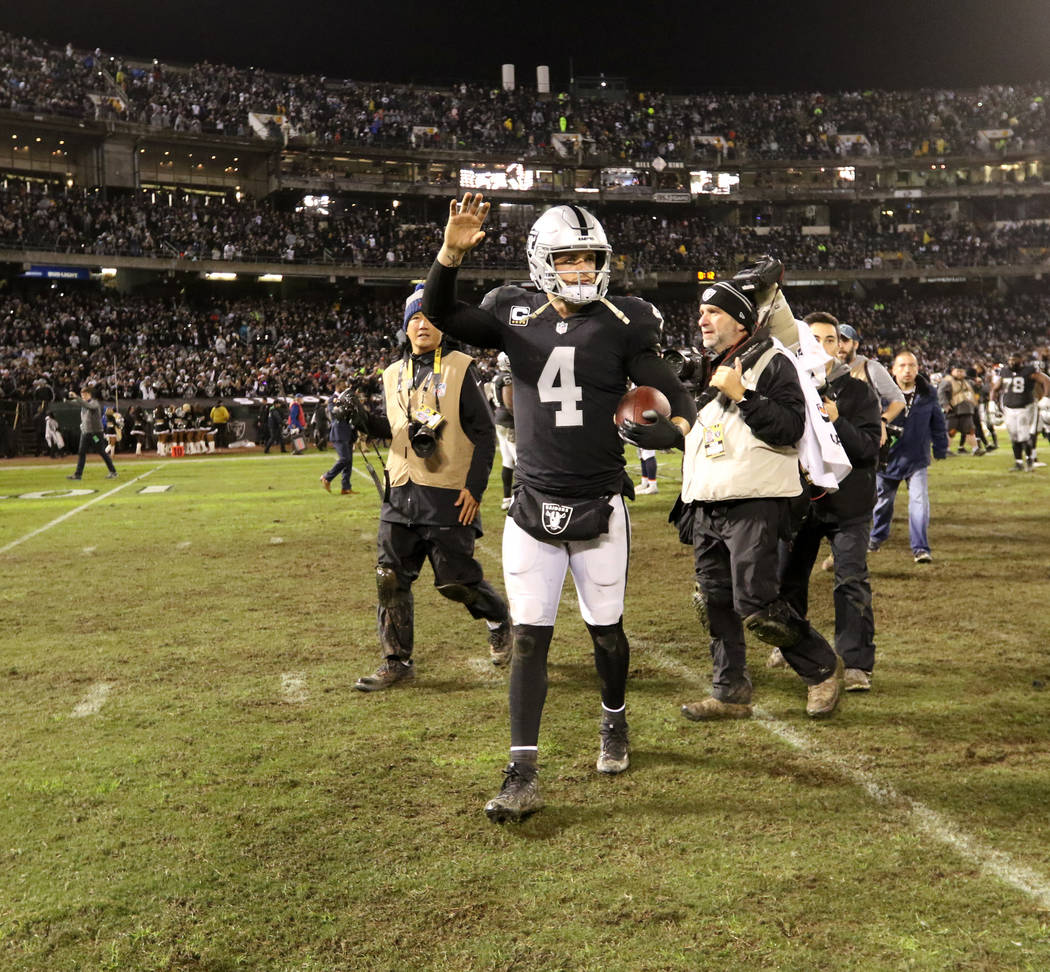 Oakland Raiders quarterback Derek Carr (4) walks on the Oakland-Alameda County Coliseum field for possibly the last time after the team's win over the against the Denver Broncos in Oakland, Calif. ...