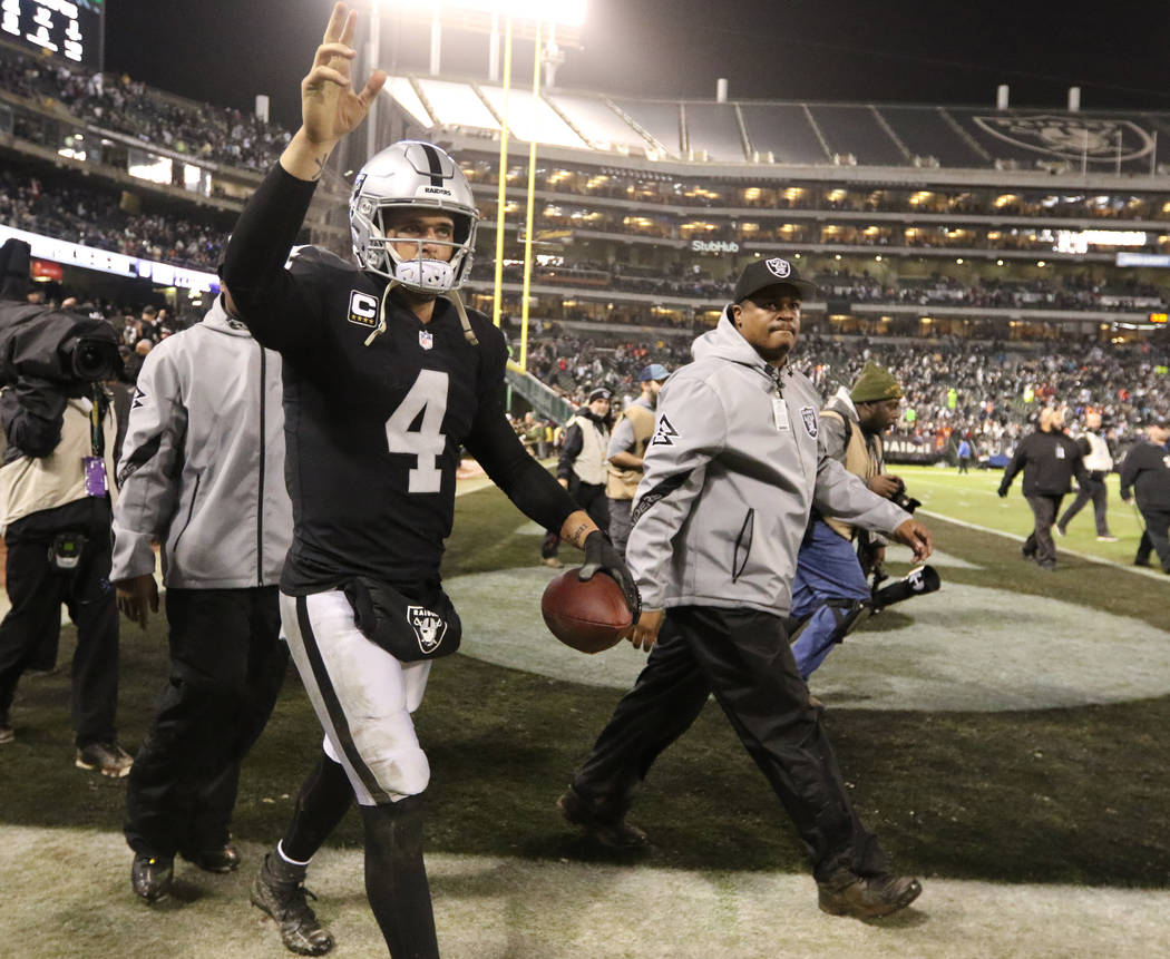 Oakland Raiders quarterback Derek Carr (4) waves to fans at the Oakland-Alameda County Coliseum field after the team's win over the against the Denver Broncos in Oakland, Calif., Monday, Dec. 24, ...