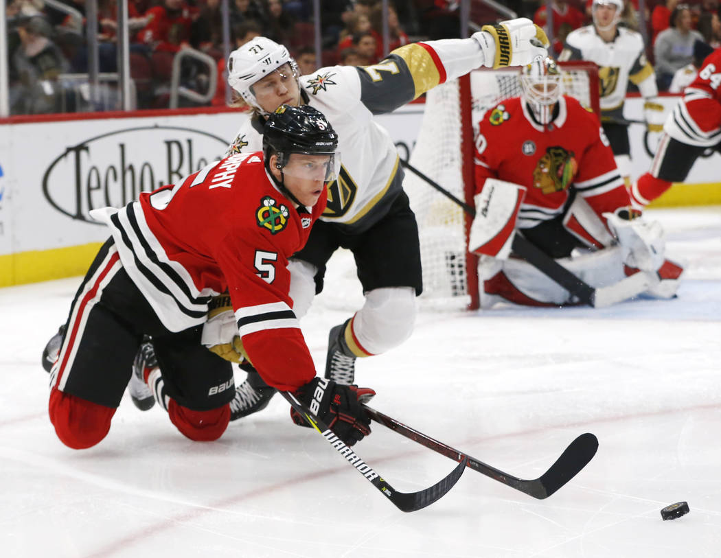 Chicago Blackhawks defenseman Connor Murphy (5) gets the puck away from Vegas Golden Knights center William Karlsson (71) during the second period of an NHL hockey game Saturday, Jan. 12, 2019, in ...