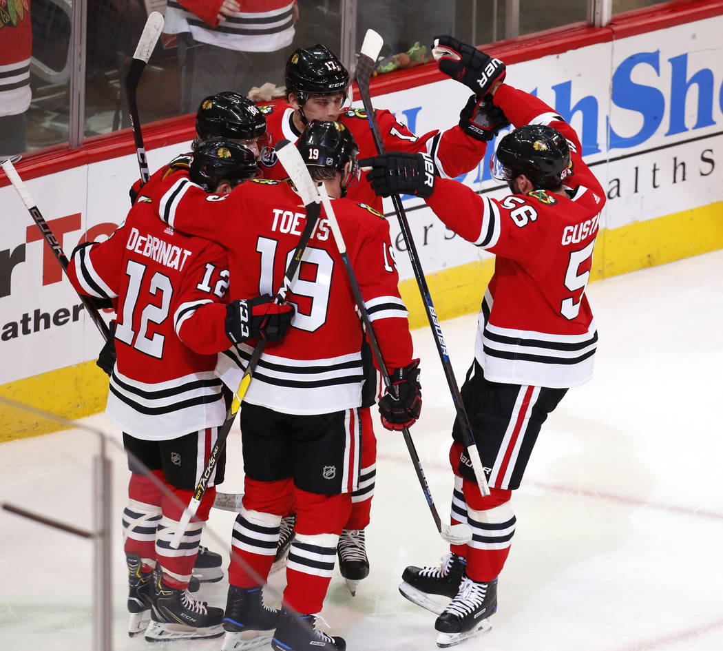 Left, Chicago Blackhawks right wing Patrick Kane (88) celebrates with teammates after his goal against the Vegas Golden Knights during the first period of an NHL hockey game Saturday, Jan. 12, 201 ...