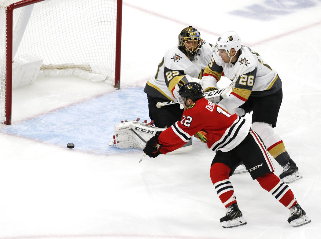 Chicago Blackhawks left wing Alex DeBrincat (12) slips the puck past Vegas Golden Knights goaltender Marc-Andre Fleury (29) for a goal during the first period of an NHL hockey game Saturday, Jan. ...