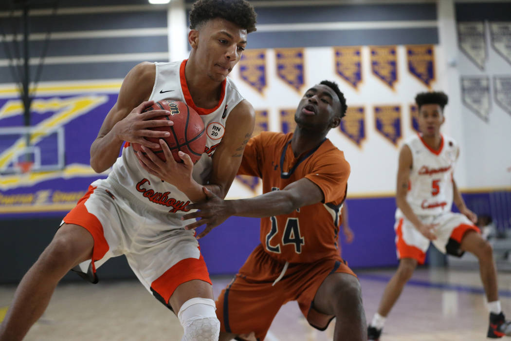 Chaparral's Sameal Anderson (24) grabs the ball against pressure from Legacy's Armani Strong (24) in the boy's basketball game at Durango High School in Las Vegas, Saturday, Jan. 12, 2019. Erik Ve ...