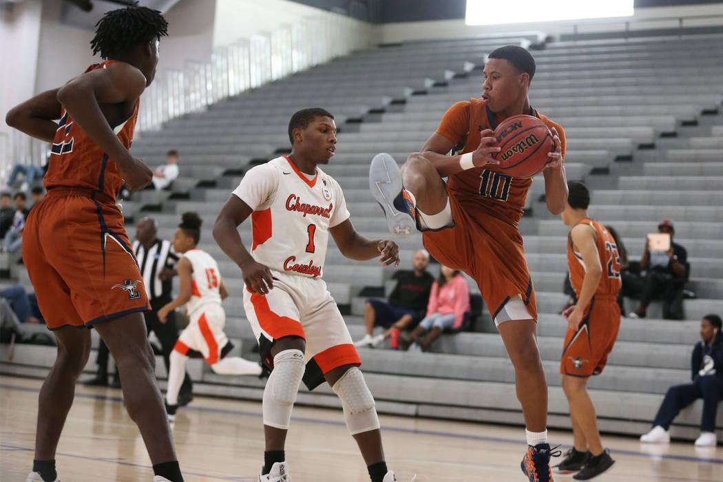 Chaparral's Meshach Hawkins (1) looks on as Legacy's Emmanuel Austin (10) grabs a rebound in the boy's basketball game at Durango High School in Las Vegas, Saturday, Jan. 12, 2019. Erik Verduzco L ...