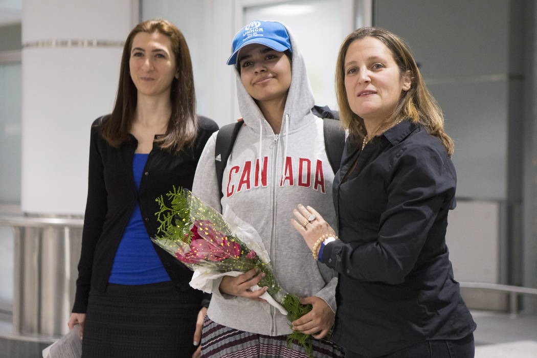 Rahaf Mohammed Alqunun, 18, center, stands with Canadian Minister of Foreign Affairs Chrystia Freeland, right, as she arrives at Toronto Pearson International Airport, on Saturday, Jan.12, 2019. ...