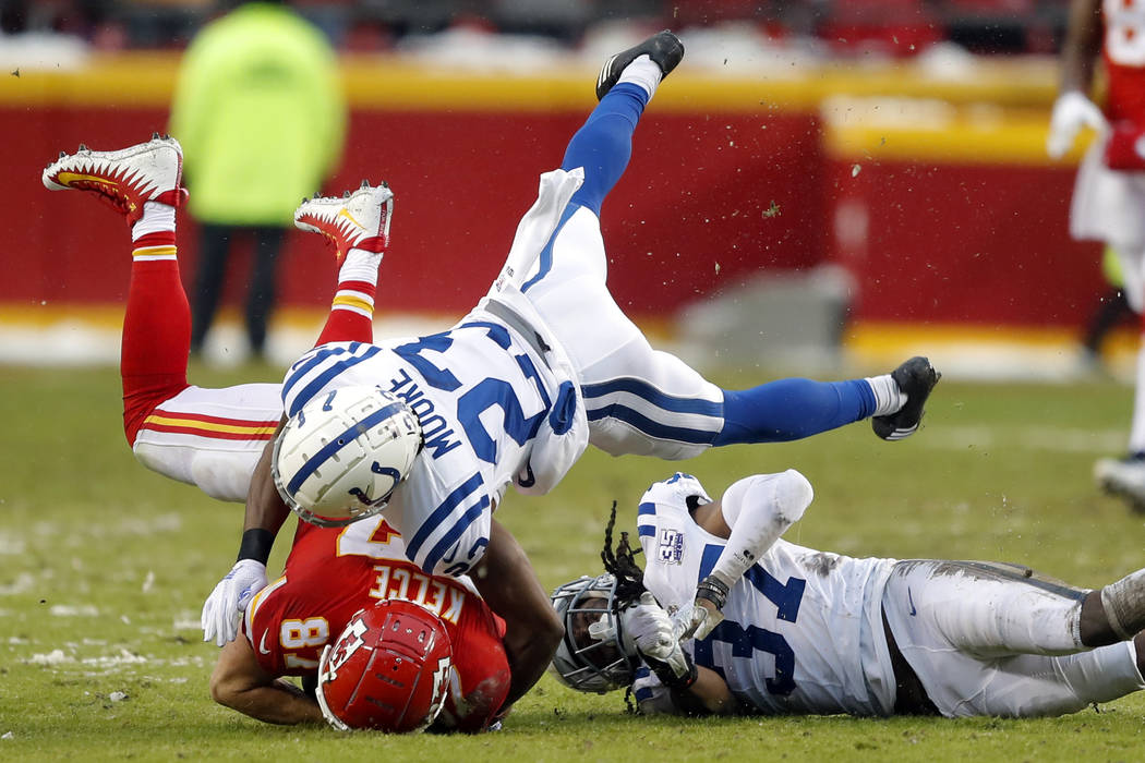 Indianapolis Colts cornerback Kenny Moore (23) tackles Kansas City Chiefs tight end Travis Kelce (87) next to defensive back J.J. Wilcox (37) during the first half of an NFL divisional football pl ...