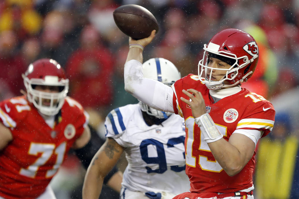 Kansas City Chiefs quarterback Patrick Mahomes (15) throws as Indianapolis Colts defensive end Jabaal Sheard (93) closes in during the first half of an NFL divisional football playoff game in Kans ...