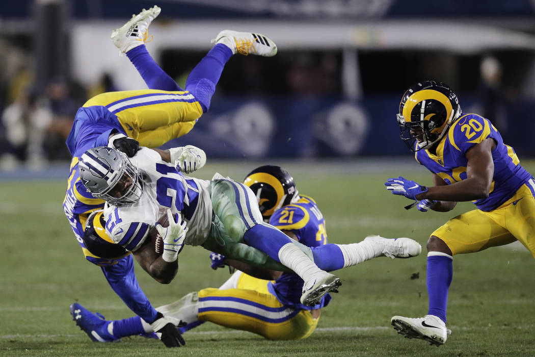 Dallas Cowboys running back Ezekiel Elliott is tackled by Los Angeles Rams linebacker Dante Fowler, top, and cornerback Aqib Talib during the second half in an NFL divisional football playoff game ...