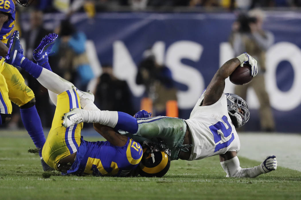 Dallas Cowboys running back Ezekiel Elliott is tackled by Los Angeles Rams cornerback Aqib Talib during the first half in an NFL divisional football playoff game Saturday, Jan. 12, 2019, in Los An ...