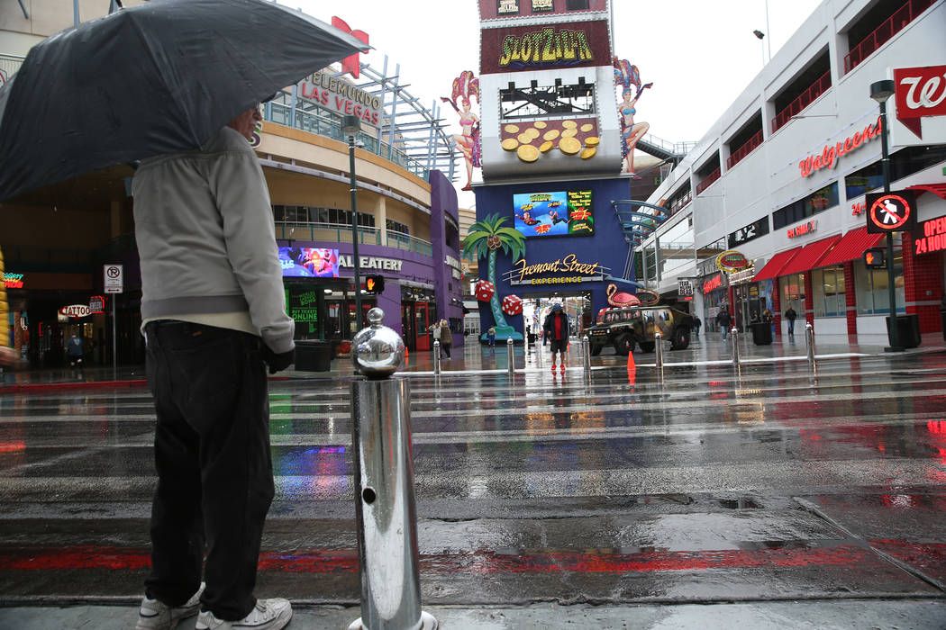 A person waits to cross the street in downtown Las Vegas as rain falls, Thursday, Nov. 29, 2018. Erik Verduzco Las Vegas Review-Journal @Erik_Verduzco