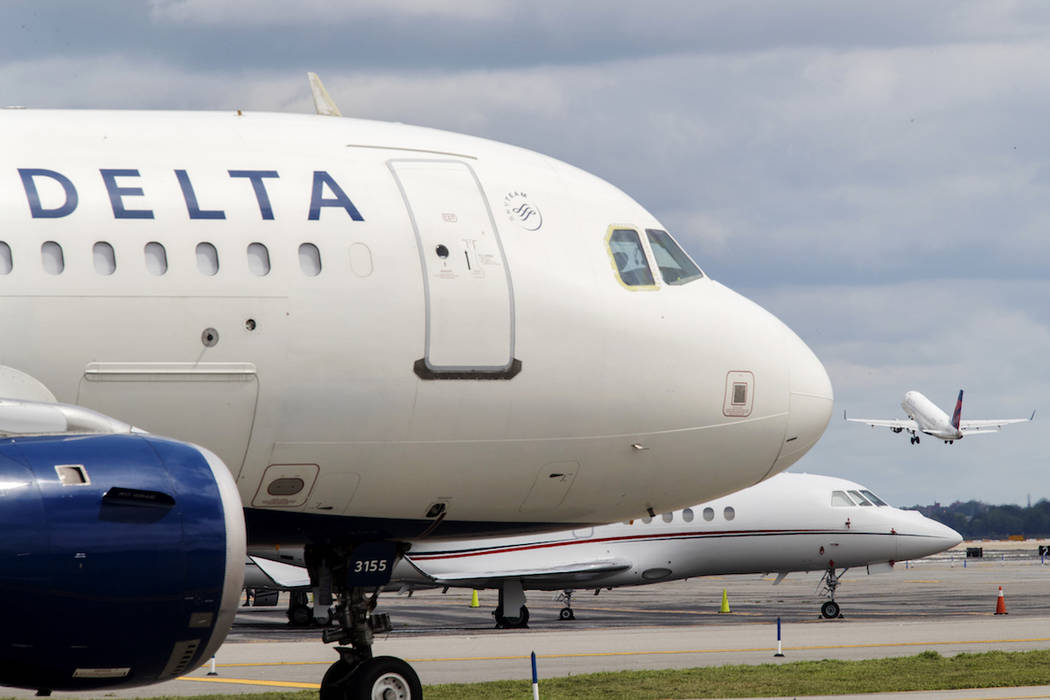 In this Tuesday, Aug. 8, 2017, photo, a Delta Air Lines airplane is seen on the tarmac as an American Air Lines takes off from LaGuardia Airport in the Queens borough of New York. (AP Photo/Mary A ...