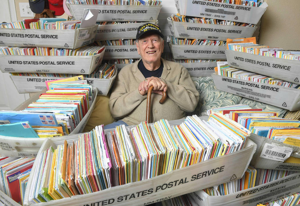 In this Tuesday, Jan. 8, 2019 photo, Duane Sherman, 96, poses at home with a small fraction of the 50,000 birthday cards he's received after his daughter's social media request for people to send ...