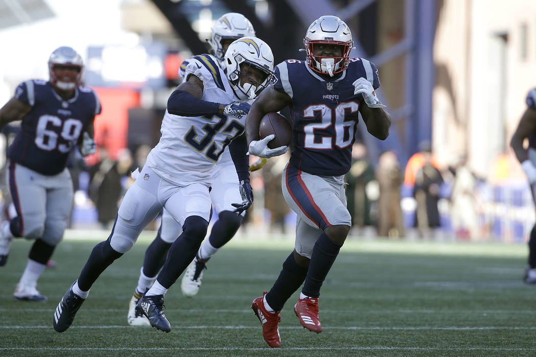 New England Patriots running back Sony Michel (26) runs away from Los Angeles Chargers free safety Derwin James (33) during the first half of an NFL divisional playoff football game, Sunday, Jan. ...