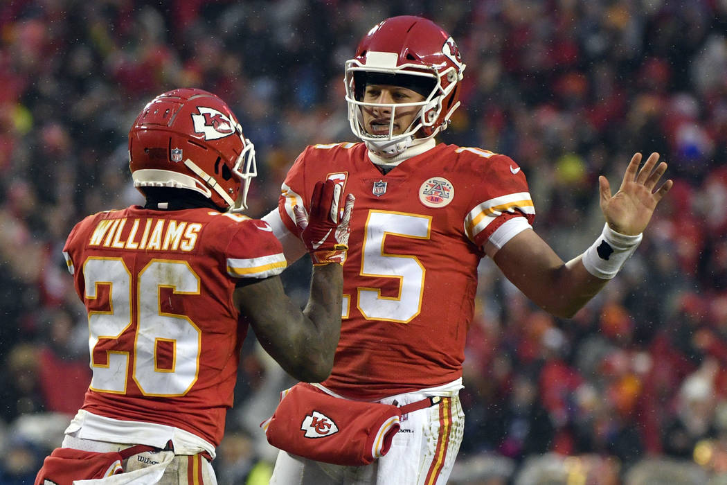 Kansas City Chiefs quarterback Patrick Mahomes (15) celebrates a touchdown with running back Damien Williams (26) during the first half of an NFL divisional football playoff game against the India ...