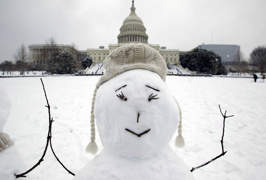 The U.S. Capitol is seen behind a snowman during a snowstorm, as a partial government shutdown stretches into its third week at Capitol Hill in Washington Sunday, Jan. 13, 2019. (AP Photo/Jose Lui ...