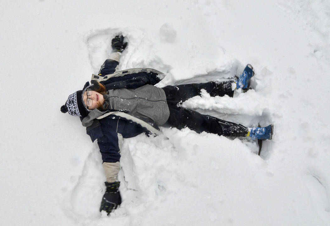 Noah Shober makes a snow angel outside of his house in Terre Haute, Ind., on Saturday, Jan. 12, 2019. A massive winter snowstorm making its way across the Midwest and into the Mid-Atlantic region ...