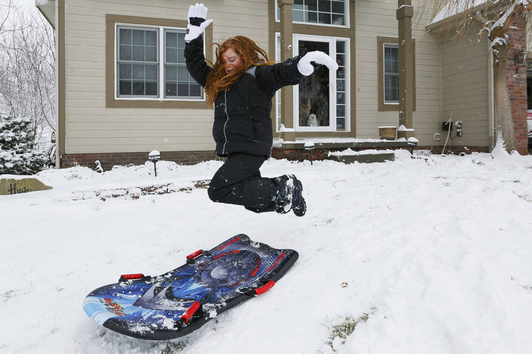 Isabella Orsini jumps into her sled as she plays in Omaha, Neb., Saturday, Jan. 12, 2019. A massive winter snowstorm moved into Kansas and Nebraska from the Rockies on Friday, then east into Misso ...