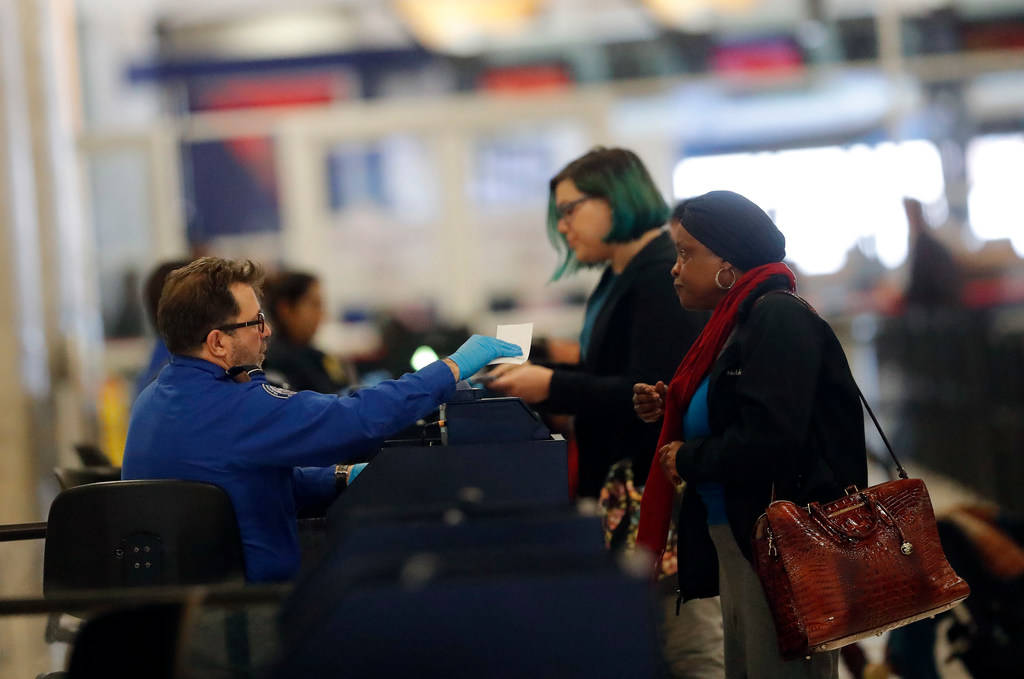 A Transportation Security Administration employee checks in air travelers at Hartsfield Jackson Atlanta International Airport Monday, Jan. 7, 2019, in Atlanta. (AP Photo/John Bazemore)