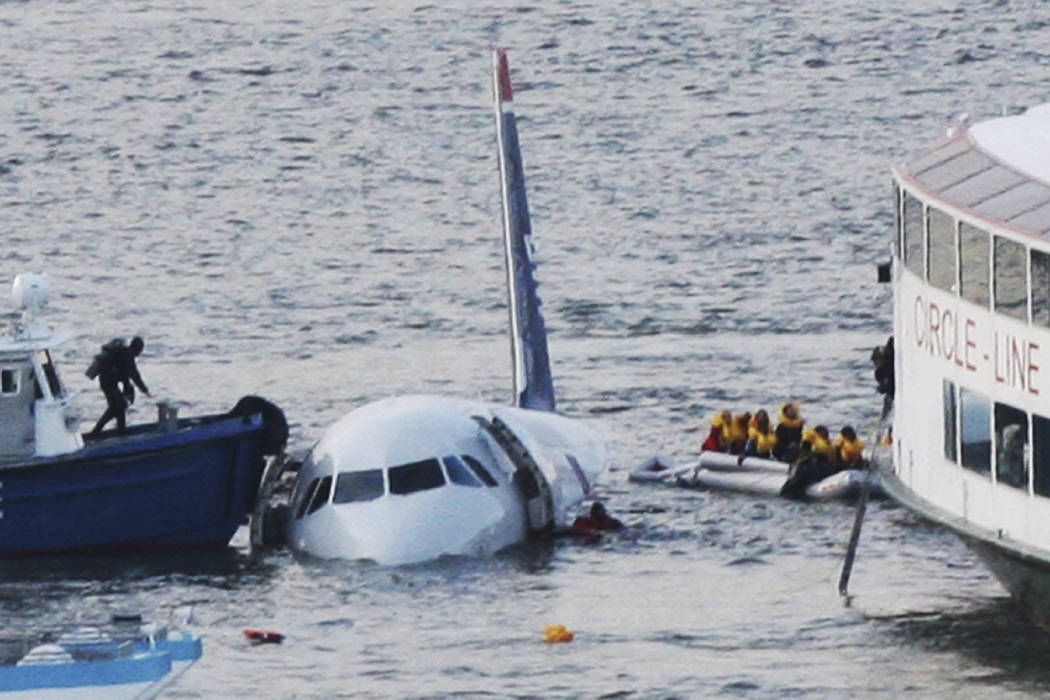 FILE - In this Jan. 15, 2009 file photo, a diver, left, aboard an NYPD vessel prepares to rescue passengers that escaped from the Airbus 320 US Airways aircraft made an emergency landing in the Hu ...