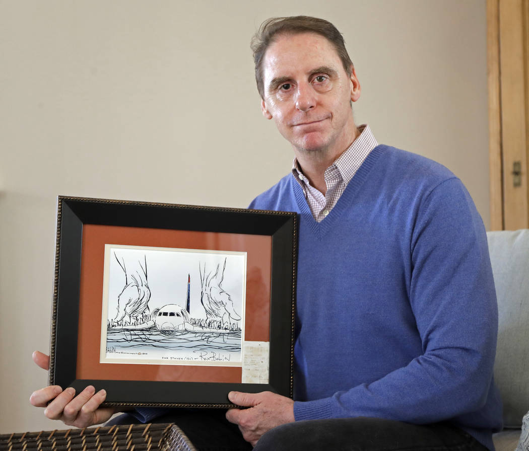 In this Jan. 10, 2019 photo, Steve O'Brien poses for a photo at his home in Charlotte, N.C., with an editorial cartoon framed with his boarding pass from US Airways Flight 1549, that eventually c ...