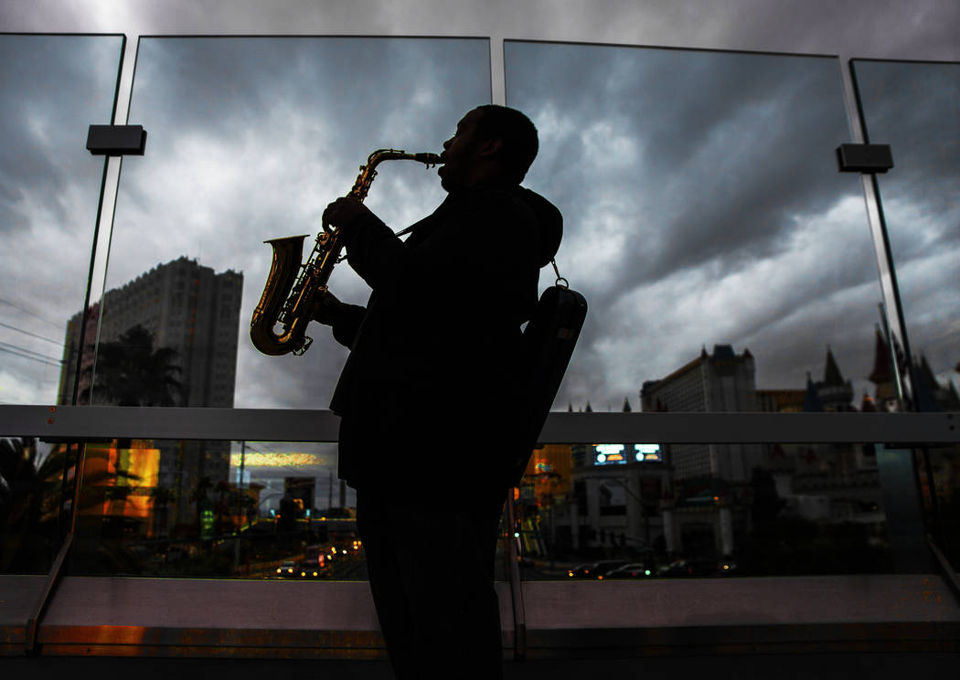 Ronald Holmes plays the alto saxophone on The Strip as dark clouds move in on Monday, Jan. 14, 2019, in Las Vegas. Clouds, rain and snow are expected in parts of the Las Vegas Valley this week. Be ...