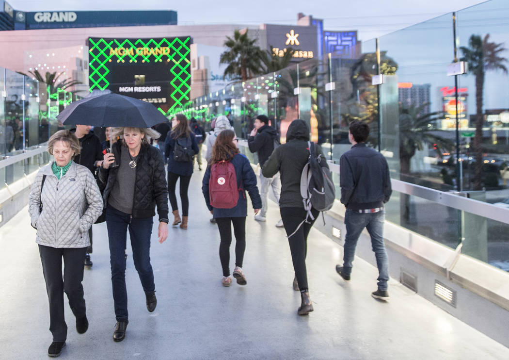 Tourists take cover as a light rain begins to fall on The Strip on Monday, Jan. 14, 2019, in Las Vegas. Clouds, rain and snow are expected in parts of the Las Vegas Valley this week. Benjamin Hage ...