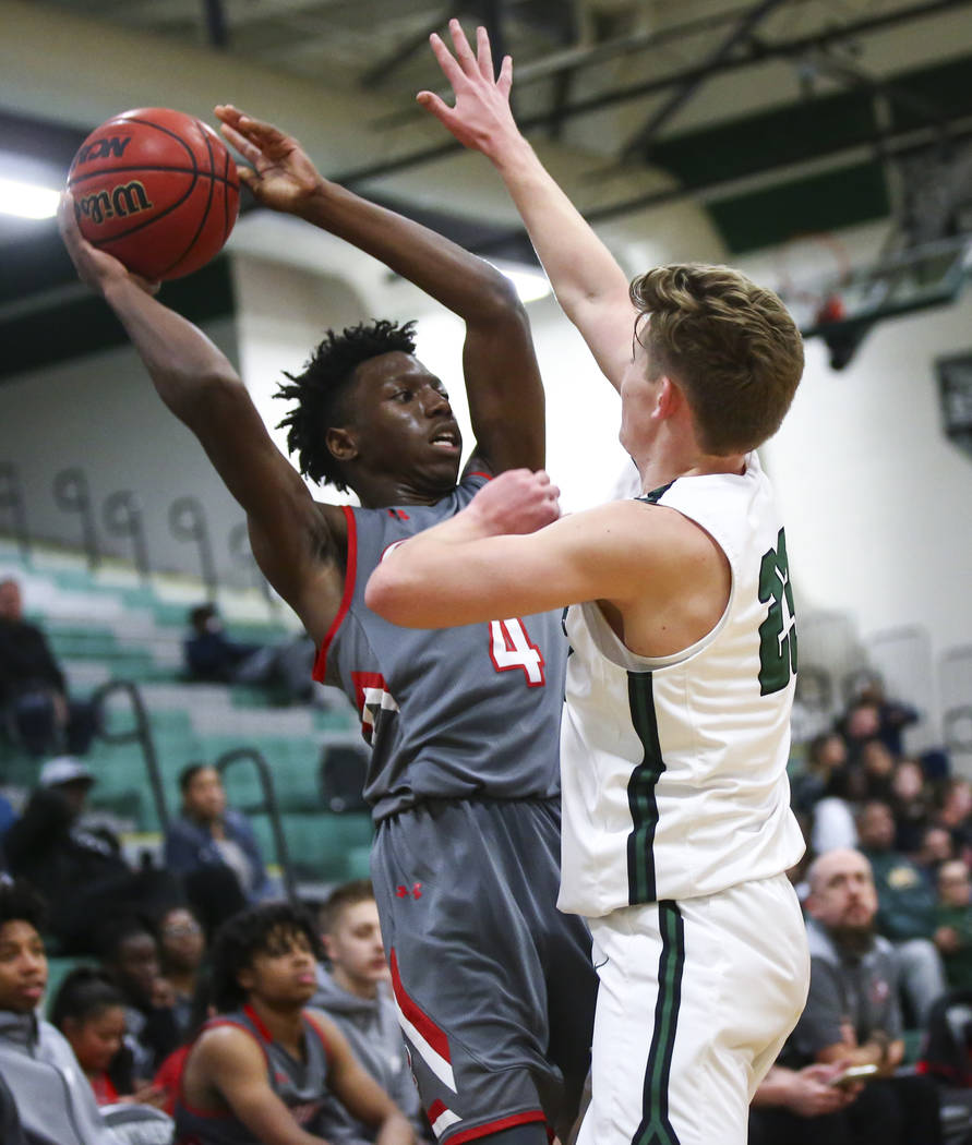 Arbor View's guard Tyre Williams (4) looks to pass the ball under pressure from Palo Verde's Kade Madsen (23) during a basketball game at Palo Verde High School in Las Vegas on Thursday, Jan. 17, ...