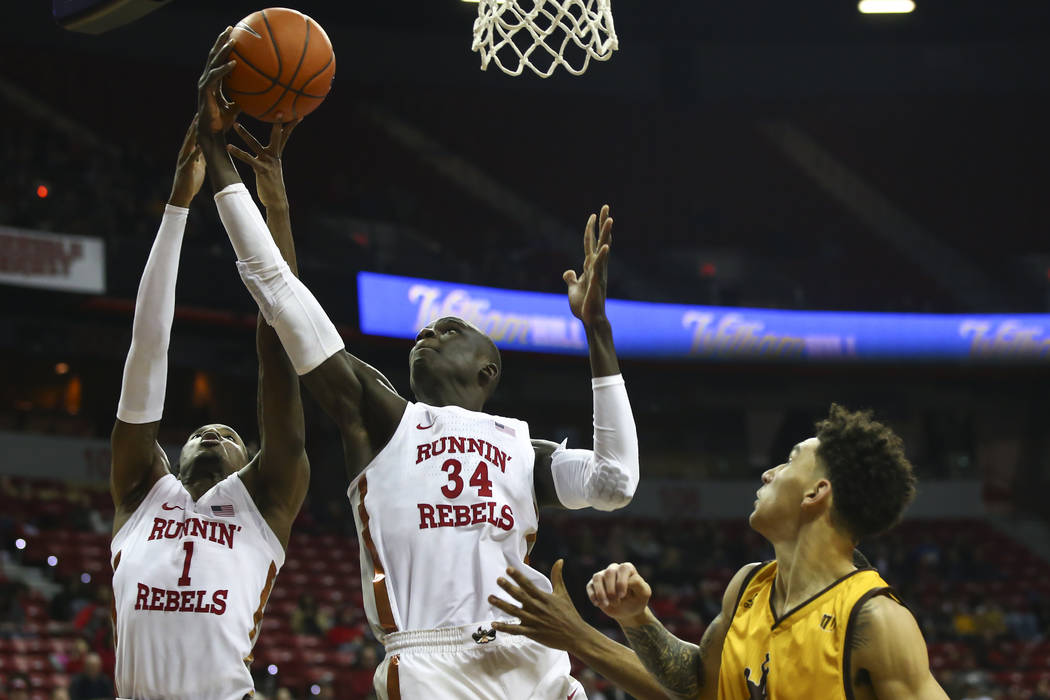 UNLV Rebels forward Cheikh Mbacke Diong (34) and UNLV Rebels guard Kris Clyburn (1) go for a rebound over Wyoming Cowboys during the first half of a basketball game at the Thomas & Mack Center ...