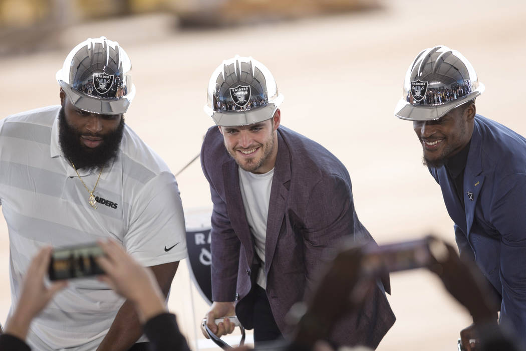 Raiders quarterback Derek Carr is flanked by teammates Justin Ellis, left, and Tahir Whitehead during a groundbreaking ceremony for the new Raiders Headquarters in Henderson on Monday, Jan. 14, 20 ...