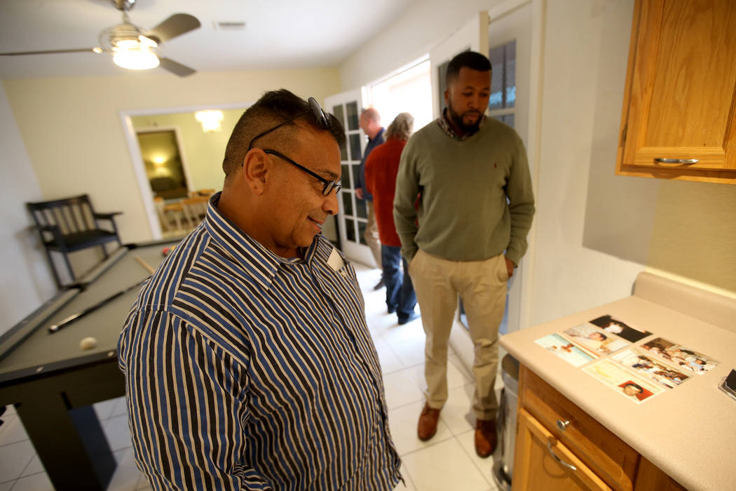 "Potential buyer Tony Redding of Las Vegas, left, checks out historical photos with broker Shannon Smith at the former home of Las Vegas mobster Tony ""The Ant"" Spilotro at 4675 Balfour Dr ..."
