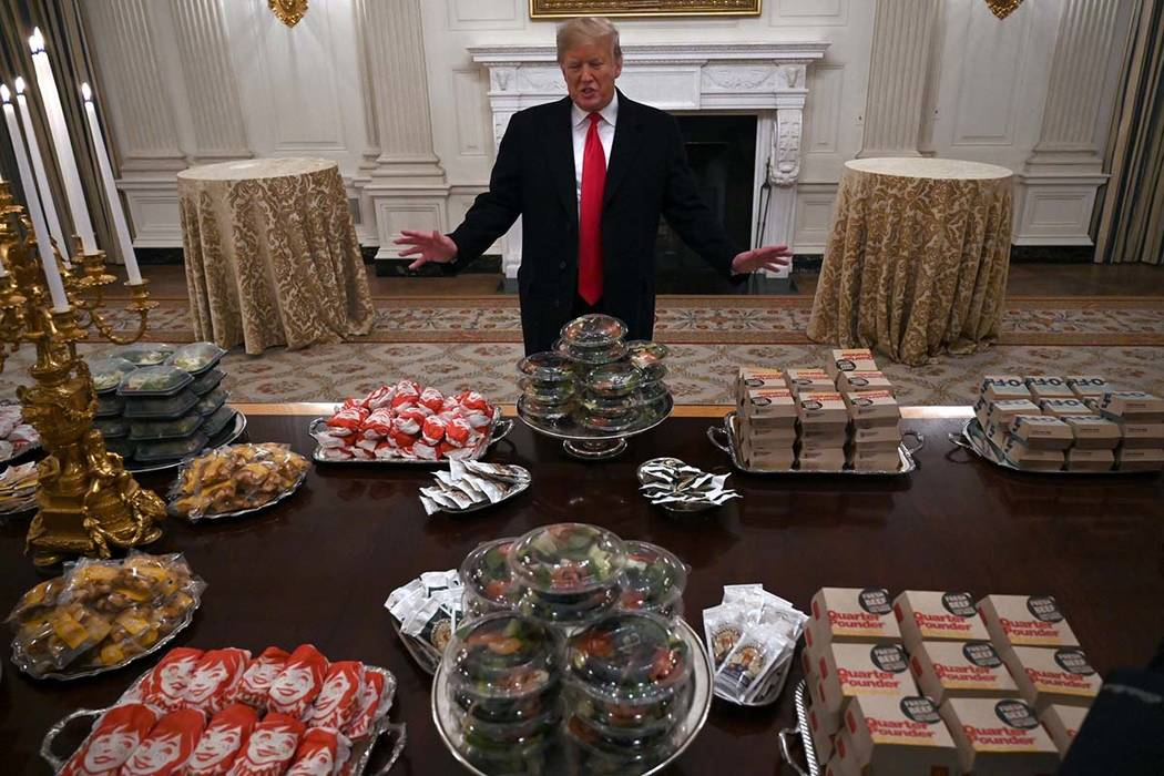 President Donald Trump talks to the media about the table full of fast food in the State Dining Room of the White House in Washington, Monday, Jan. 14, 2019, for the reception for the Clemson Tige ...
