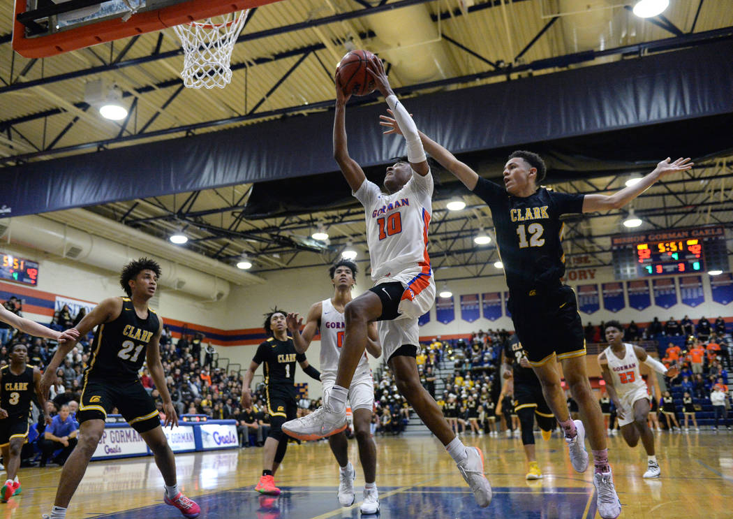 Bishop Gorman's Zaon Collins (10) goes to shoot the ball while under pressure from Clark's Cameron Kimble (12) during the second half of a basketball game at Bishop Gorman High School in Las Vegas ...