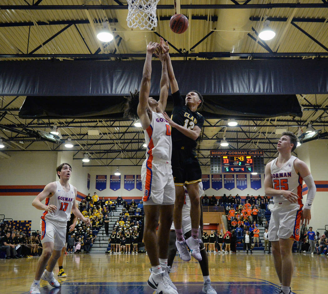 Clark's Cameron Kimble (12) goes to shoot the ball while under pressure from Bishop Gorman's Isiah Cottrell (0) during the first half of a basketball game at Bishop Gorman High School in Las Vegas ...