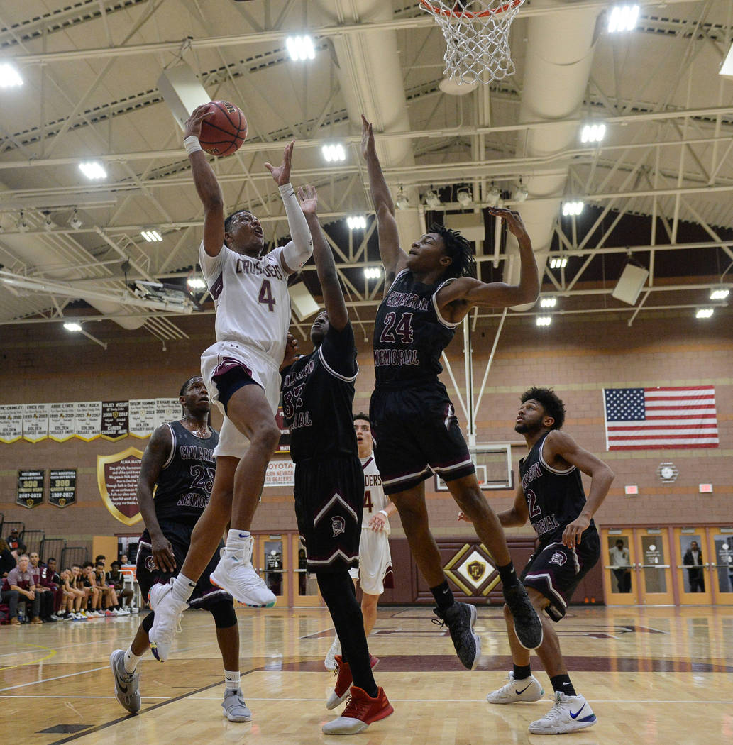Faith Lutheran's Sedrick Hammond (4) goes to shoot the ball while under pressure from Cimarron Memorial's Tyrek Williams (32) and Isaiah Profit (24) during the second half of a basketball game at ...